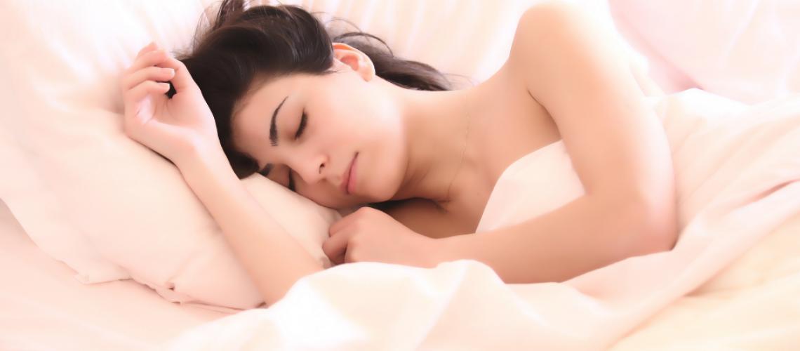 Mujer durmiendo en la cama con tapones para dormir a medida